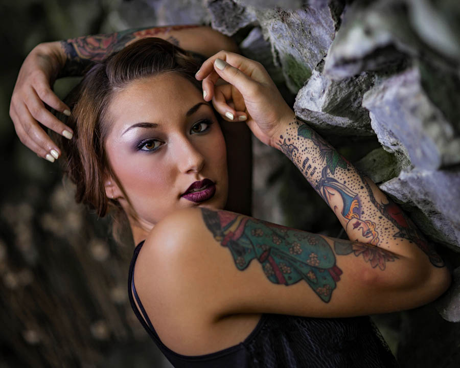 asian woman model with tattoos in a cave with rocks