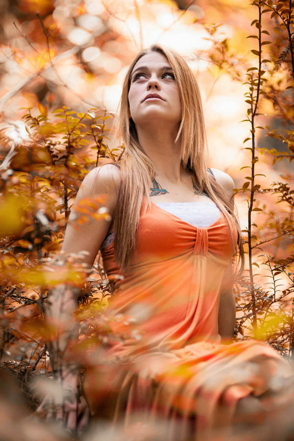 outdoor portrait young woman sitting in forest with bright sunlight